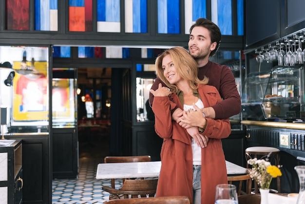 Lustiges schwules paar, das sich umarmt und zur seite schaut