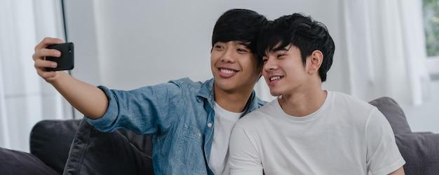 Lustiges selfie der romantischen jungen homosexuellen paare durch mobiltelefon zu hause. der asiatische männliche liebhaber, der glücklich ist, entspannen sich den spaß, der das technologiehandylächeln einsetzt, machen ein foto zusammen beim lügensofa im wohnzimmer.