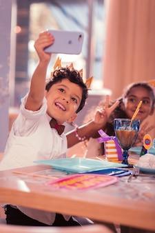 Lustiges selfie. fröhlicher emotionaler junge, der glücklich lächelt, während er modernes smartphone hoch hält und selfies mit freunden nimmt