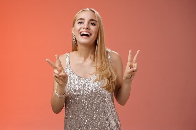 Lustiges sorgloses charmantes kaukasisches blondes weibliches modell im silbernen stilvollen glamourkleid zeigen friedenssieggeste, die breit lächelnd viel spaß hat, geburtstagsfeier zu feiern, stehenden roten hintergrund.