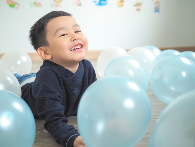 Lustiges spiel des kleinen jungen mit bunten ballonen