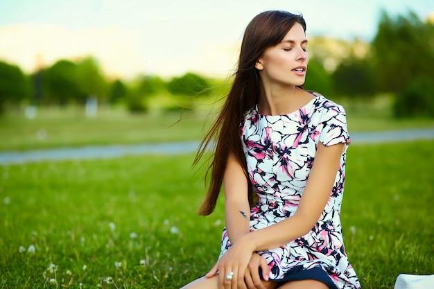 Lustiges stilvolles lächelndes schönes junges frauenmodell im hellen sommerkleid des hutes im hut im park
