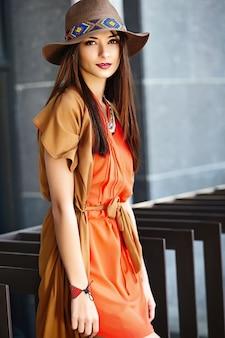 Lustiges stilvolles sexy lächelndes schönes junges hippie-frauenmodell im sommer hellen hipster-kleidungskleid in der straße im hut