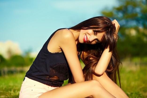 Lustiges stilvolles sexy lächelndes schönes schönes sonnenbadmodell der jungen frau im hellen hippen hipster-stoff des sommers, der im park auf gras sitzt