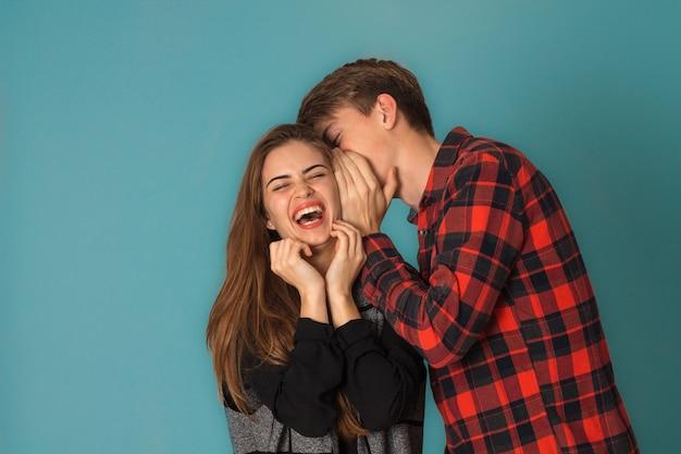 Lustiges stilvolles verliebtes paar, das spaß im studio auf blauem hintergrund hat