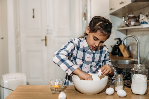 Lustiges süßes kleines mädchen, das teig in der küche vorbereitet. kind backt kekse in der küche zu hause.