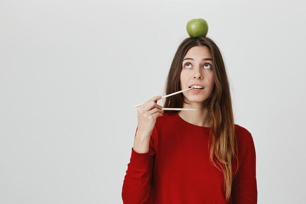 Lustiges süßes mädchen mit apfel auf kopf beißen essstäbchen, wollen essen. konzept zum mitnehmen