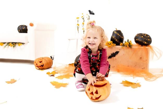 Lustiges und süßes kleines blondes kurvenmädchen mit kürbis in der halloween-dekoration