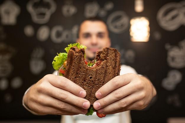Lustiges unscharfes porträt der nahaufnahme des griffs des jungen mannes gebissenes sandwich durch seine zwei hände.