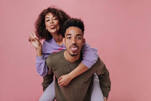 Lustiges verliebtes paar, das zungen zeigt. mädchen in lila outfit mit friedenszeichen an rosa wand