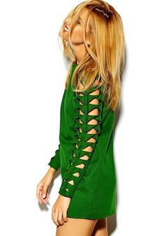 Lustiges verrücktes glamouröses stilvolles sexy lächelndes schönes blondes junges frauenmodell in grüner hipster-kleidung im studio