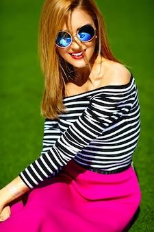 Lustiges verrücktes glamouröses stilvolles sexy lächelndes schönes blondes junges frauenmodell in rosa hipster-kleidung, die im gras im park sitzt