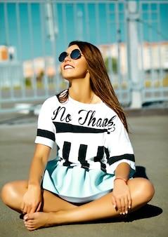 Lustiges verrücktes glamouröses stilvolles sexy lächelndes schönes junges frauenmodell im hellen hipster-sommer lässigen stoff, der in der straße hinter blauem himmel sitzt