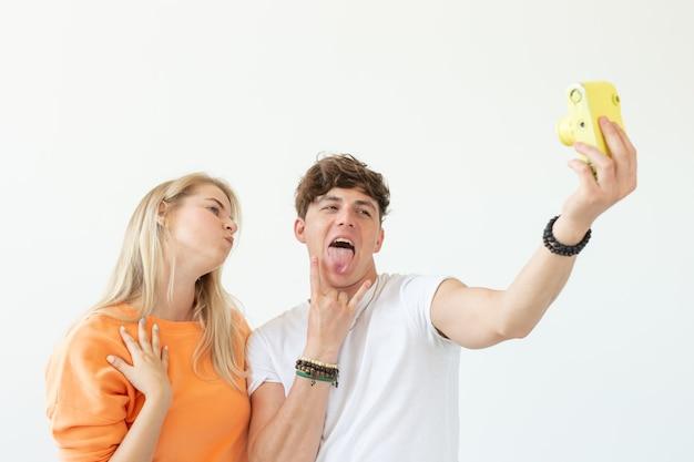 Lustiges verrücktes junges paar blondes mädchen und ein hipster-typ, der ein selfie auf einem gelben weinlesefilm nimmt