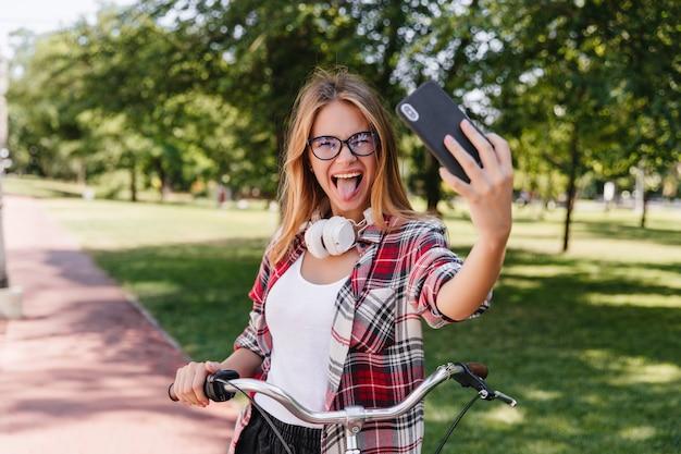 Lustiges weibliches modell, das im park mit zunge heraus aufwirft. außenporträt des aktiven mädchens auf dem fahrrad, das selfie mit lächeln macht.