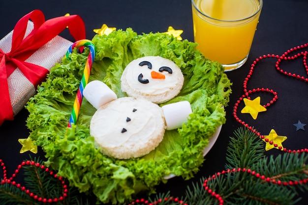 Lustiges weihnachtsfrühstück, sandwiches, schneemann, regenbogenbonbons, marshmallow.