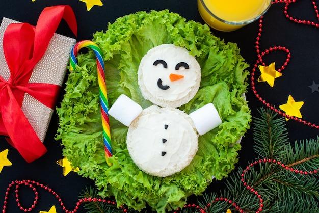Lustiges weihnachtsfrühstück, sandwiches, schneemann, regenbogenbonbons, marshmallows.