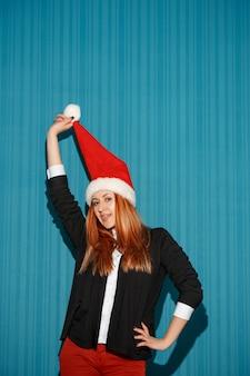 Lustiges weihnachtsmädchen, das eine weihnachtsmütze auf dem blauen studiohintergrund trägt