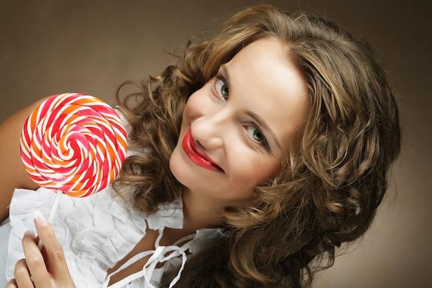 Lutscher in der hand. schönes lockiges mädchen mit süßigkeiten.
