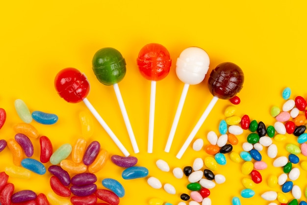 Lutscher und süßigkeiten der draufsicht färbten süß auf gelbe, zuckersüße süßwaren lokalisiert