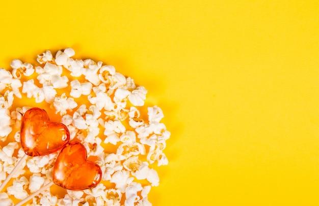 Lutscher und verstreutes popcorn auf gelbem hintergrund.