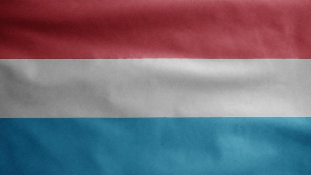 Luxemburger fahnenschwingen im wind. nahaufnahme von luxemburg banner weht, weiche und glatte seide. stoff textur fähnrich hintergrund. verwenden sie es für das konzept für nationalfeiertage und länderanlässe.