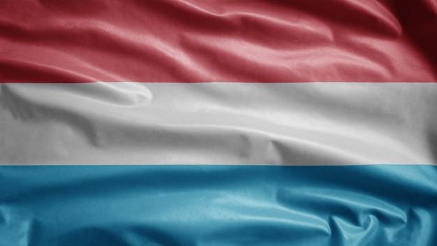 Luxemburger fahnenschwingen im wind. nahaufnahme von luxemburg banner weht, weiche und glatte seide. stoff textur fähnrich hintergrund.