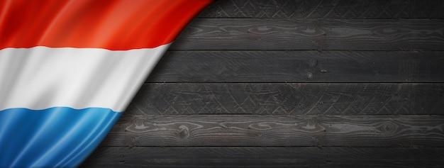 Luxemburger flagge auf schwarzer holzwand. horizontales panorama-banner.