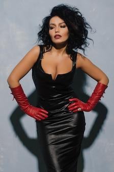 Luxuriöse asiatische frau, die im schwarzen lederkleid und in den roten handschuhen aufwirft. dominante fetisch lady.