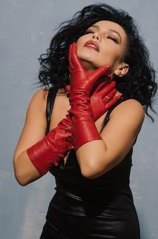 Luxuriöse asiatische frau im schwarzen lederkleid und in den roten handschuhen, die sich am hals halten. dominante fetisch lady.