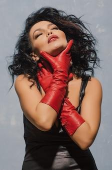 Luxuriöse asiatische frau im schwarzen lederkleid und in den roten handschuhen, die sich am hals halten.