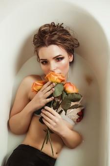 Luxuriöse blonde dame mit hellem make-up nimmt ein bad mit milch und rosen auf ihrem körper