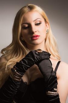 Luxuriöse blonde frau in schwarzem spitzenkorsett und seidenhandschuhen, die im studio posiert. schatten und licht