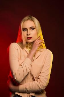 Luxuriöse blonde frau mit hellem make-up. rotes und gelbes studiolicht