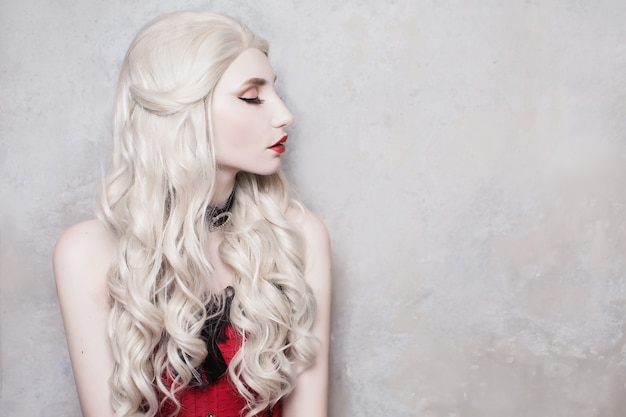 Luxuriöse blonde frau mit schönen langen weißen haaren und roten lippen auf einem grauen hintergrund.