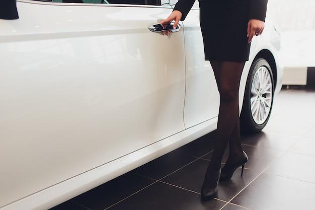 Luxuriöse dame, die mit offener tür im weißen auto sitzt.