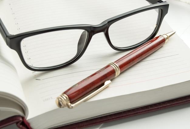 Luxuriöse herrenaccessoires - stilvolle schwarze brille und ein stift auf einem offenen tagebuch, nahaufnahme