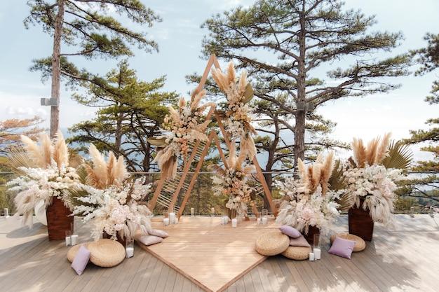 Luxuriöse hochzeitszeremonie im boho-stil auf dem hintergrund des waldes und des ozeans.