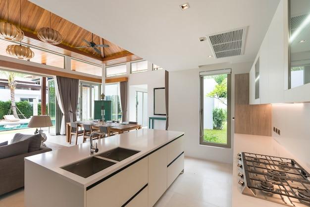 Luxuriöse innenarchitektur im küchenbereich, die mit einer theke und eingebauten möbeln ausgestattet ist
