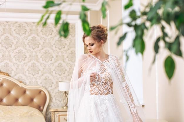 Luxuriöse junge schöne glückliche braut in einem modischen hochzeitskleid im schlafzimmer