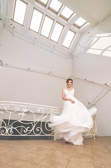 Luxuriöse junge schöne glückliche braut in einem modischen hochzeitskleid in einem großen weißen raum