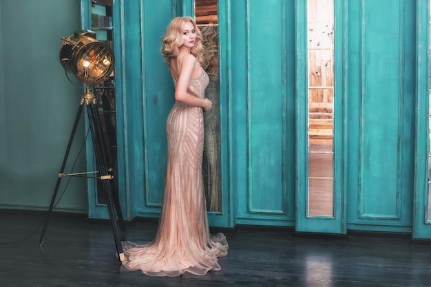 Luxuriöse junge schöne vorbildliche blonde frau in einem schicken langen goldkleid im innenraum