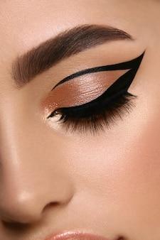 Luxuriöse weibliche make-up-nahaufnahme mit eyeliner und goldenem lidschatten