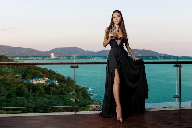 Luxuriöser brunette, der in einem schwarzen langen kleid im teuren schmuck mit einem glas weinbalkon aufwirft. luxuriöse aussicht auf die tropische insel und das meer
