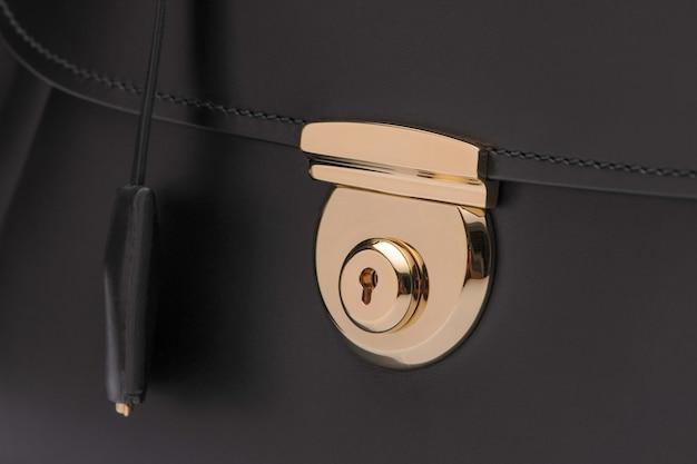 Luxuriöser goldener verschluss an schwarzer ledertasche, nahaufnahme