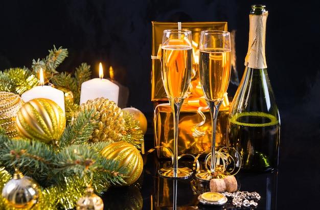 Luxuriöser goldener weihnachtshintergrund mit einer flasche und gläsern champagner, geschenk, dekorationen und brennenden kerzen auf dunklem hintergrund