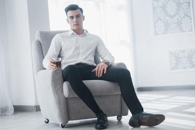 Luxuriöser stilvoller mann. junger eleganter kerl im weißen anzug sitzt auf dem stuhl und hält glas mit alkohol.