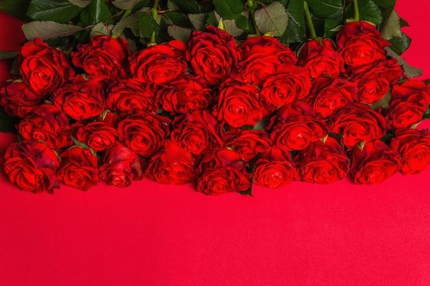 Luxuriöser strauß frischer roter rosen. das festliche konzept für hochzeiten, geburtstage, 8. märz, mutter- oder valentinstag. grußkarte, roter matter hintergrund