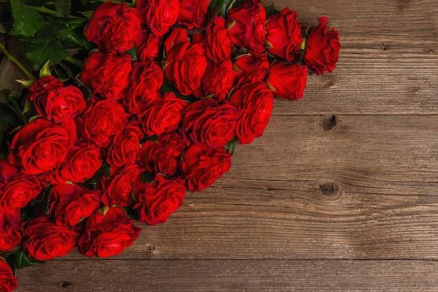 Luxuriöser strauß frischer roter rosen. das festliche konzept für hochzeiten, geburtstage, 8. märz, mutter- oder valentinstag. grußkarte, vintage holztisch