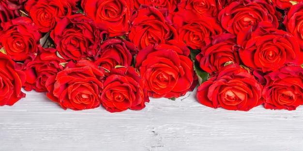 Luxuriöser strauß frischer roter rosen. das festliche konzept für hochzeiten, geburtstage, 8. märz, mutter- oder valentinstag. grußkarte, weiße holztafeln, banner